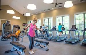 Four women working out in fitness center on fitness equipment