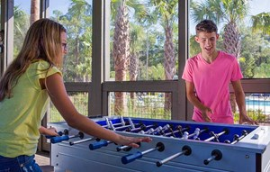 A boy and girl playing foosball in an open-air game room