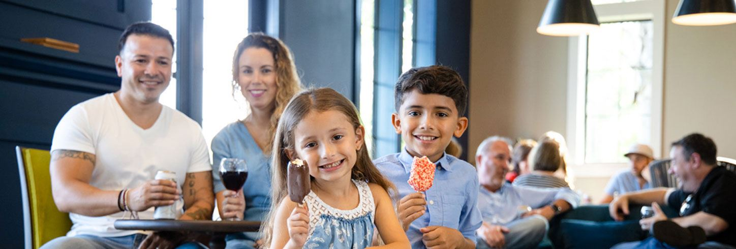 Family enjoying happy hour with drink for the grownups and ice cream treats for kids.